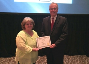 Joyce Beck receives a certificate to recognize her 34 years of service from Alabama Nursing Home Association Executive Director Bill O'Connor at Alabama's Best Practices 2014.