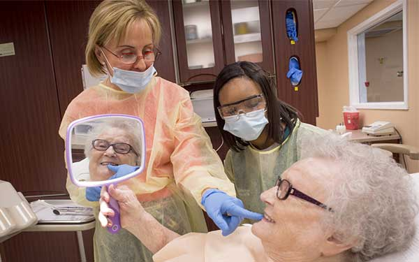 A UAB dental instructor and student provide dental care to a resident of Fair Haven Retirement Community. Photo Credit: Steve Wood, University of Alabama at Birmingham.