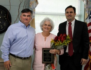 Cam DeArman, left, and Mark DeArman present their mother Martha Burns DeArman with a plaque and flowers to recognize her dedication to Burns Nursing & Rehab.
