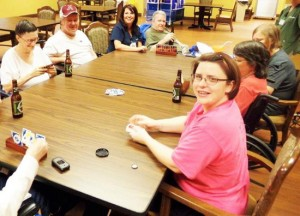 Marshall Manor Nursing Home residents and staff play cards while sipping non-alcoholic beer.