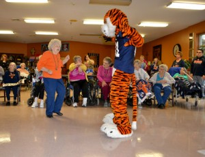 Aubie teaches residents how to dance at Albertville Nursing Home & Rehab Select.